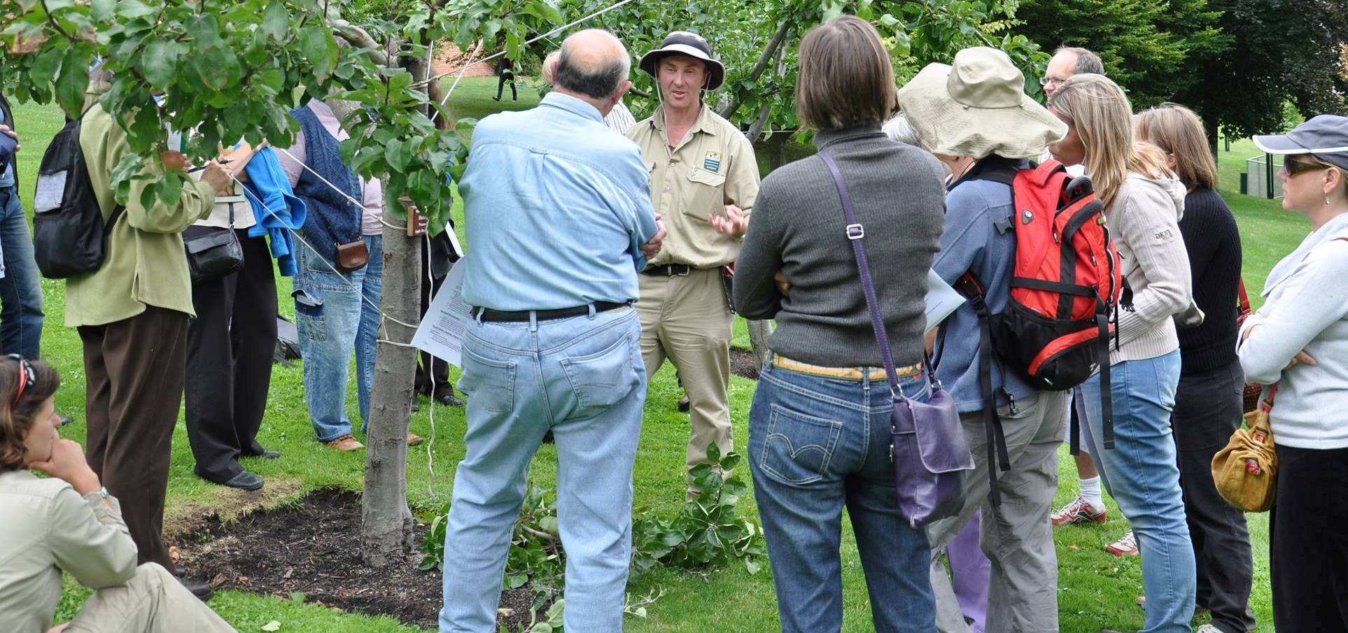 Gardens presenter talking to a group of day students around and apple tree