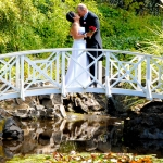 wedding couple embracing on the arch bridge over the lily pond
