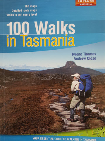 Image of the front cover of the book 100 walks in Tasmania, by Tyrone Thomas and Andrew Close. Image of man on mountain trail central Tasmania and mountain in the background
