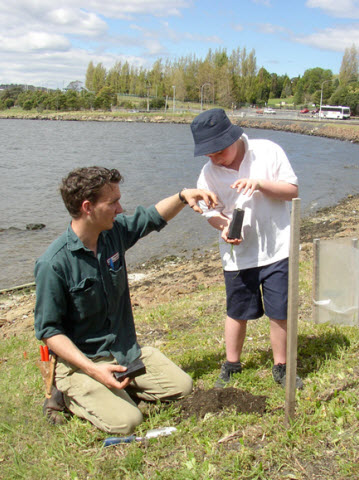 Primary student helps assess the sites condition for planting on the foreshore